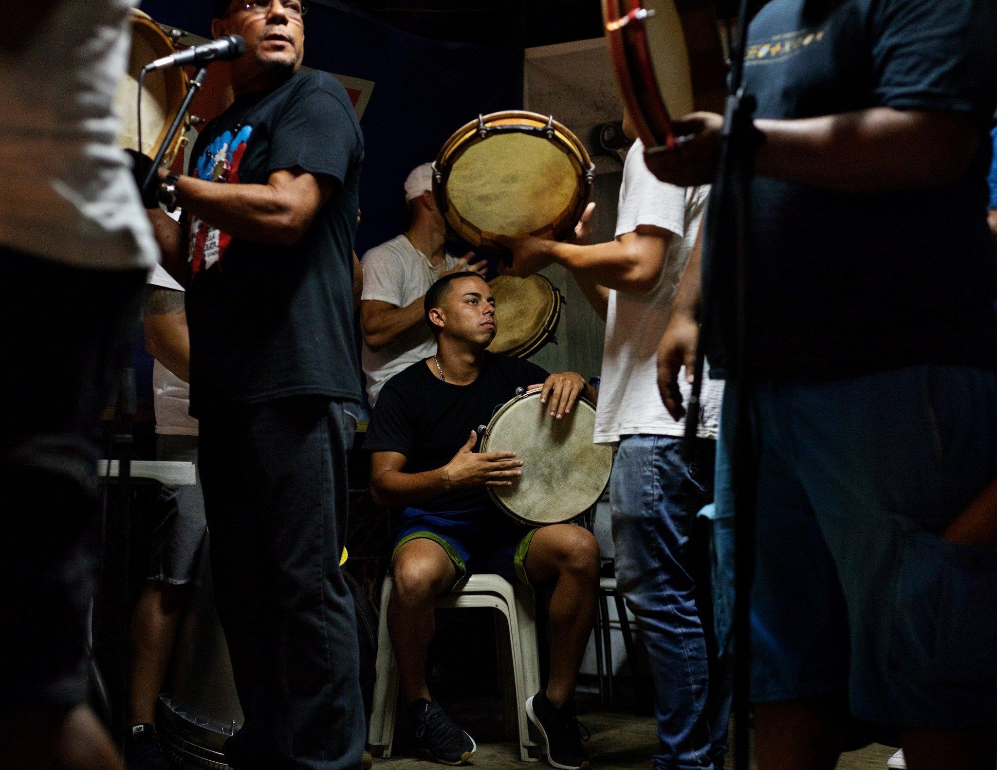 Foto de muchacho tocando pandero de plena puertorriqueña - Llevan un cancionero navideño a las parrandas.