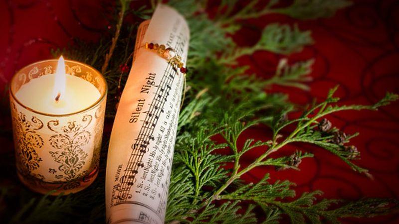 Vela y partitura musical de la canción Noche de Paz